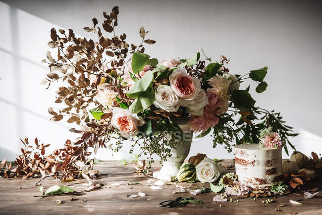 Dish with tasty cake decorated bloom bud on wooden table with bunch of chrysanthemums, roses and plant twigs in vase between dry leaves on grey background — Stock Photo