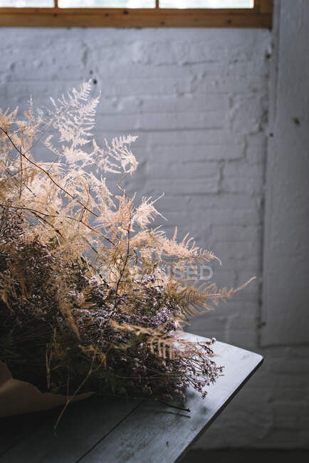 Concept of bouquet of dry coniferous twigs in craft paper on table near stool in grey murk room with brick walls — Stock Photo
