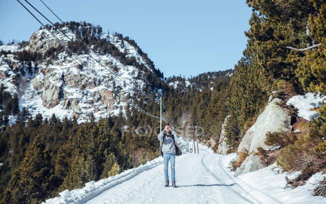 Joven macho tomando fotos en el teléfono móvil y de pie en la carretera entre las montañas en la nieve en Cerdanya, Francia - foto de stock