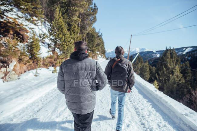 На задньому плані чоловіки йдуть сільською стежкою між горами у сніговій місцевості Серданья (Франція). — стокове фото