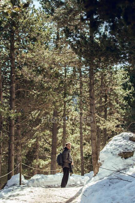 Joven con gafas de sol y gorra con mochila mirando hacia otro lado mientras sostiene una cámara profesional entre el bosque de invierno en Cerdanya, Francia - foto de stock