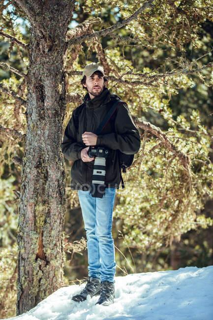 Молодий чоловік у сонцезахисних окулярах і кришці з рюкзаком, що відвернувся, тримаючи в руках професійну камеру між зимовими лісами в Серданья (Франція). — стокове фото