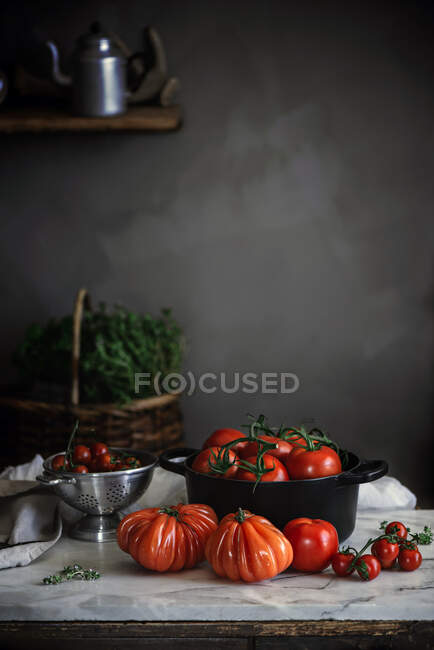 Big red ripe tomatoes of different forms in pot on table near grey wall — Stock Photo