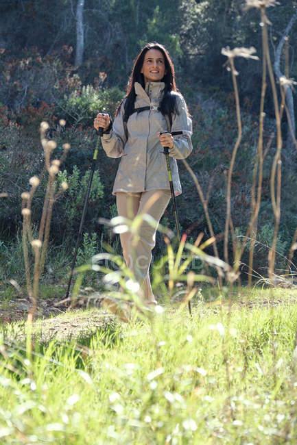 Senhora alegre em casaco caminhando com trekking paus no caminho na floresta em dia ensolarado — Fotografia de Stock