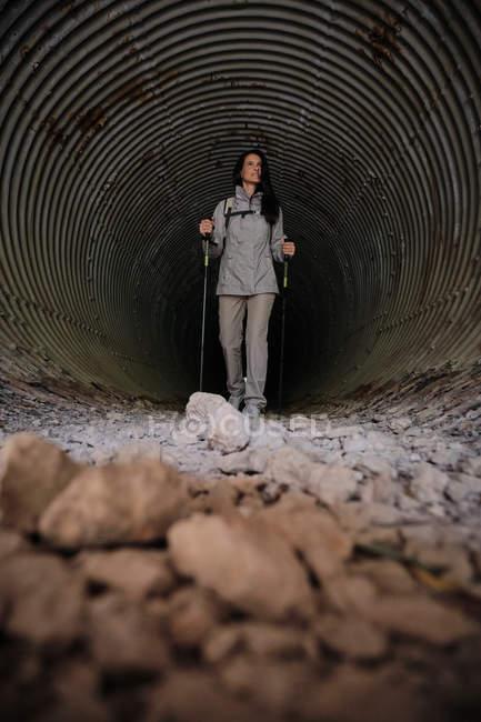 Mulher feliz com paus de trekking no túnel escuro — Fotografia de Stock