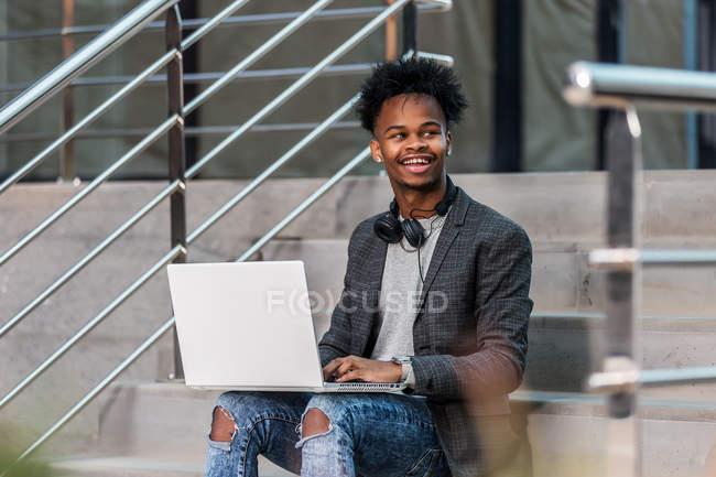 Homem de negócios preto com laptop sentado na rua da cidade — Fotografia de Stock