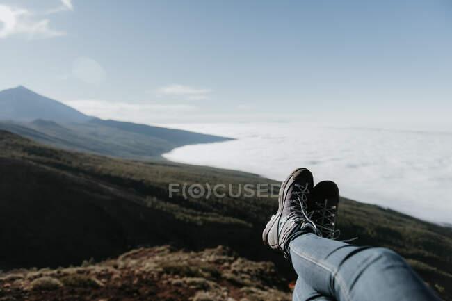 Gambe ritagliate di turista irriconoscibile sdraiato e rilassante sulla cima della collina — Foto stock