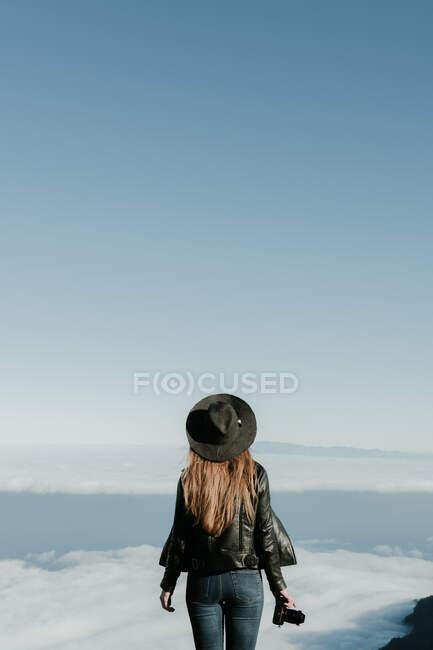 Позаду жінка з фотокамерою, що стоїть на вершині пагорба і дивиться на хмарний пейзаж. — стокове фото