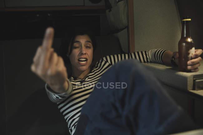 Junge brünette betrunkene Frau zeigt Mittelfinger und hält Flasche Bier in Mobilheim — Stockfoto