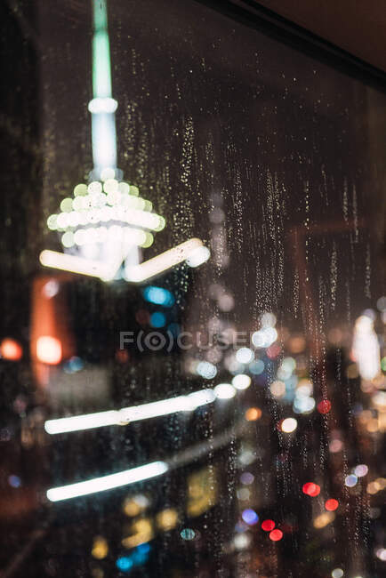 Blurred view of brightly illuminated modern city through wet window glass at rainy night in Dubai — Stock Photo