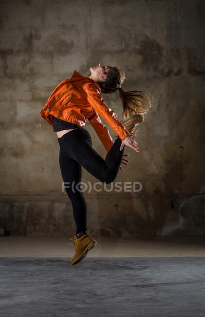 Вид сбоку на юную леди в повседневной одежде, прыгающую с ноги на спину в серой мрачной комнате — стоковое фото