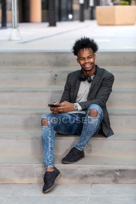 Черный бизнесмен со смартфоном сидит на городской улице — стоковое фото