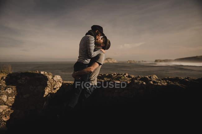 Уздовж берега біля скель, біля моря, з чарівним небом, милується стильна пара. — стокове фото