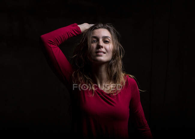 Young woman dancing in darkness — Stock Photo