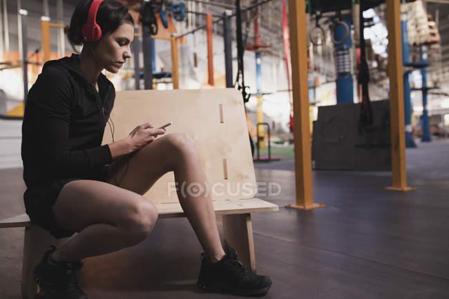 Vue latérale de la jeune femme en vêtements de sport avec écouteurs et gadget écouter de la musique et assis dans la salle de gym — Photo de stock