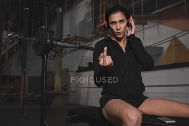 Woman in sportswear with headphones and smartphone listening music, showing middle finger and sitting on bench press — Photo de stock