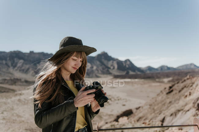 Female photographer standing and looking at the camera in desert — Stock Photo