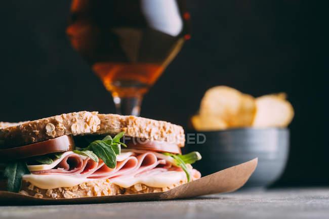 Köstliches Sandwich mit Schinken, Käse und Grüns mit Glas Bier und Chips auf dunklem Hintergrund — Stockfoto