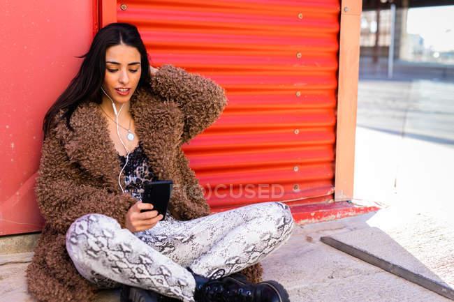 Donna alla moda con smartphone vicino alla parete — Foto stock