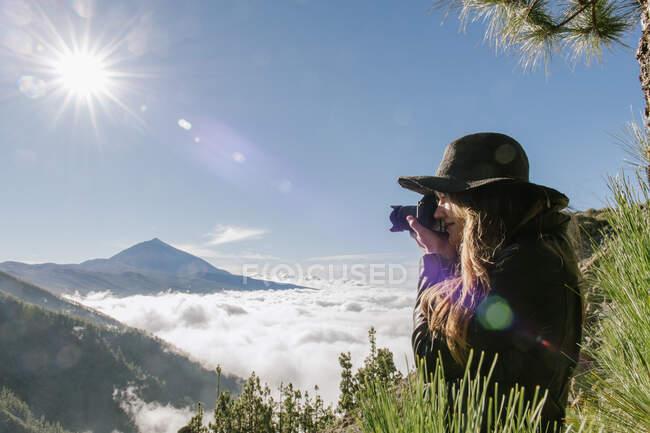 У сонячний день на вершині пагорба стоїть жіночий фотограф, який фотографує небо на тлі хмар. — стокове фото