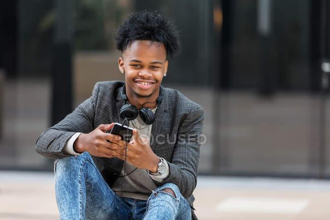 Homme d'affaires noir avec smartphone assis sur la rue de la ville — Photo de stock