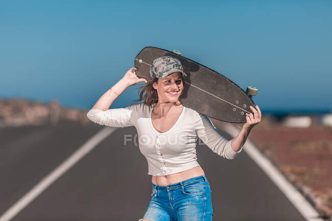 Happy lady with long board posing on asphalt road — Stock Photo