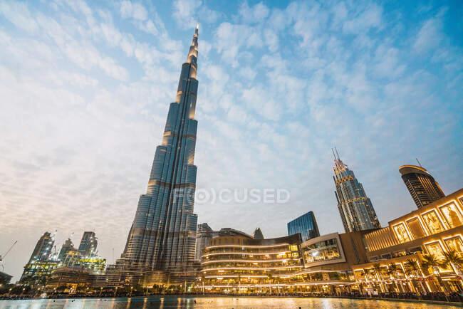 D'en bas ciel bleu avec des nuages blancs sur les gratte-ciel contemporains éclairés sur la rue de Dubaï — Photo de stock