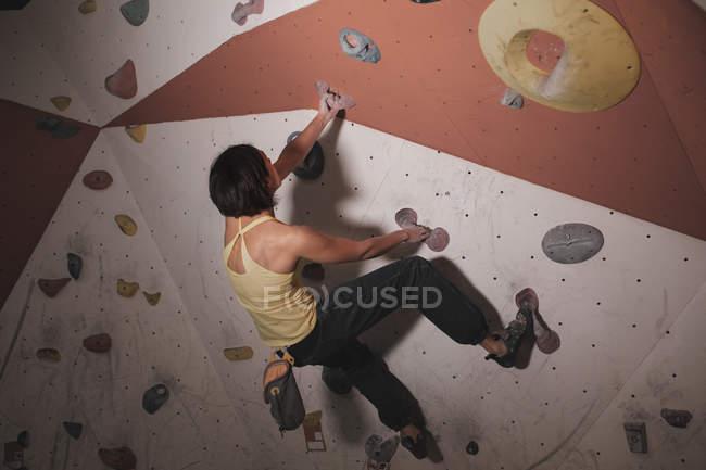 Vista posteriore della donna in allenamento di abbigliamento sportivo su parete da arrampicata con prese in palestra — Foto stock
