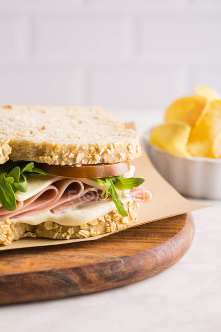 Delicious sandwich with ham, cheese and greens on wooden chopping board with potato chips — Stock Photo