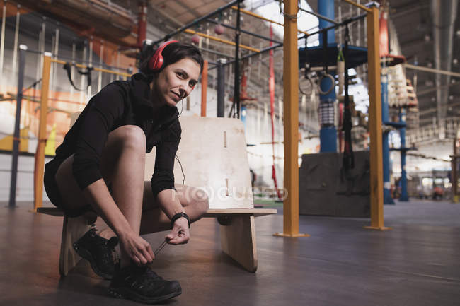 Side view of woman in sportswear with headphones listening music and lacing shoe in gym — Photo de stock