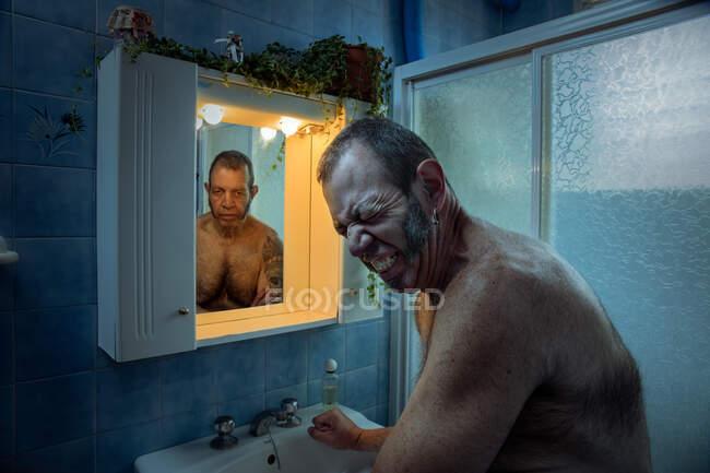 Hombre maduro frunciendo el ceño por el dolor y el estrés mientras está de pie en el baño con autorreflexión en el espejo mirando deprimido - foto de stock