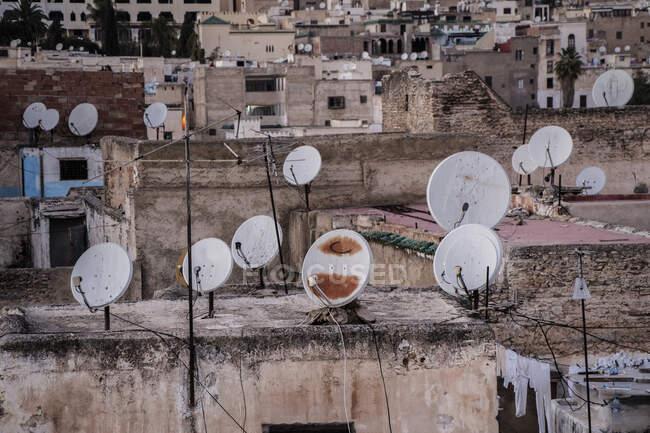 Muchas antenas satélite en los tejados de casas antiguas en la ciudad de Marrakech, Marruecos - foto de stock