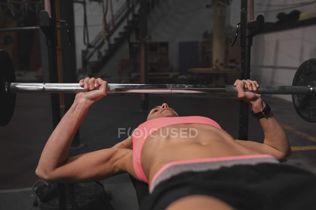 Woman in sportswear doing exercises with barbells on bench press in gym — Foto stock