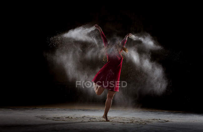 Молодая женщина танцует и использует порошок в темноте — стоковое фото