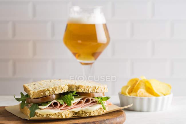 Смачний бутерброд з шинкою, сиром і зеленню зі склом пива і чіпсами на білому фоні — стокове фото