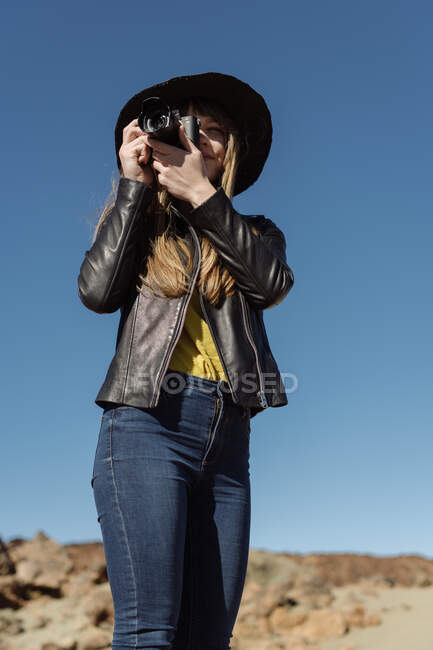 Female photographer standing with camera and looking at hills in desert — Stock Photo