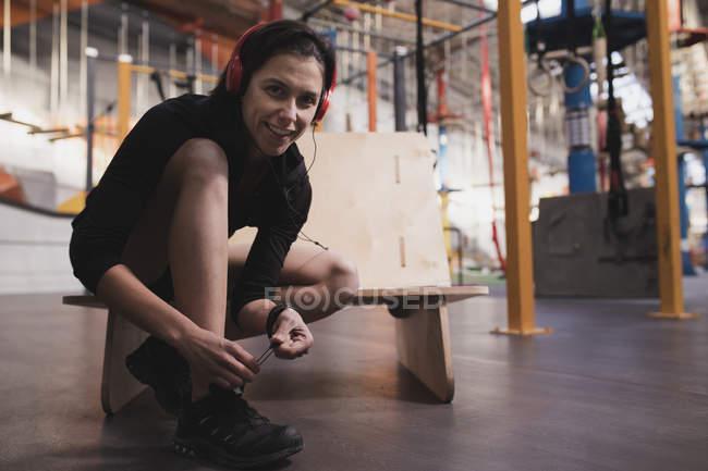 Vue latérale de la femme en vêtements de sport avec écouteurs écoutant de la musique et chaussures de laçage dans la salle de gym — Photo de stock