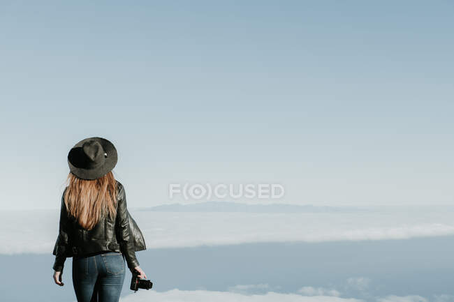 Back view of woman with photo camera standing on the top of the hill and looking at cloudscape — Stock Photo