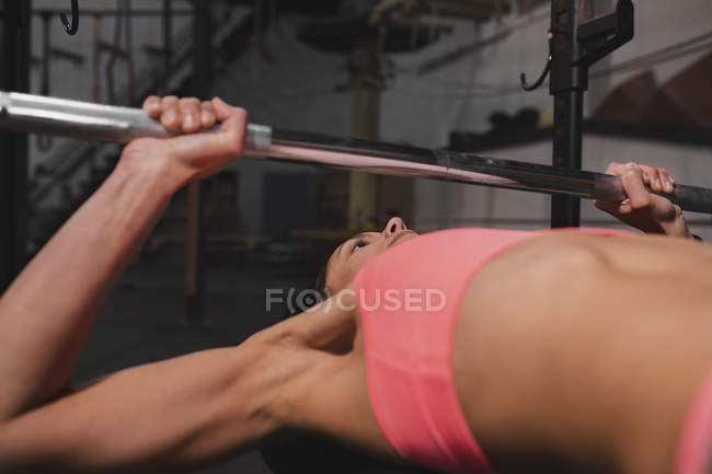 Woman in sportswear doing exercises with barbells on bench press in gym — Stock Photo