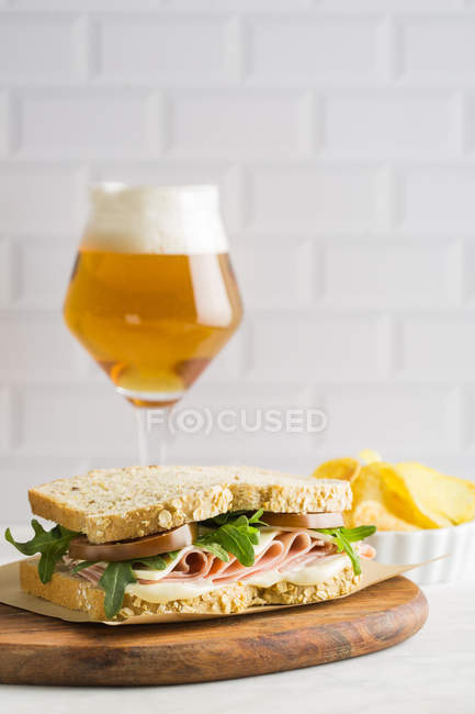 Delicious sandwich with ham, cheese and greens with glass of beer and chips on white background — Stock Photo