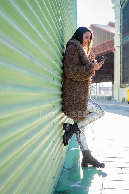 Напружена жінка зі смартфоном біля стіни. — стокове фото