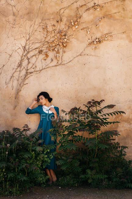 Belle femme arabe en robe entre les plantes près du mur — Photo de stock