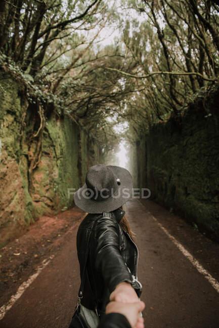 З боку погляд на елегантну леді в капелюсі і шкіряний піджак, тримаючи за руку людину і стоячи на стежці між муром алеї високих стін і лісу. — стокове фото
