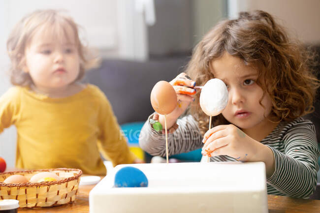 Sisters painting Easter eggs at home — Stock Photo