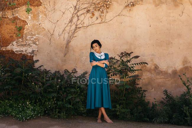 Mulher de vestido azul com as mãos cruzadas em pé perto de plantas verdes crescendo perto da parede de pedra envelhecida — Fotografia de Stock