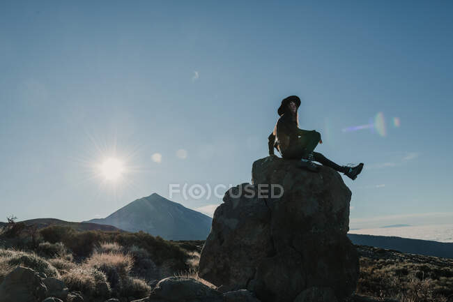 Side view of unrecognizable traveller woman sitting on rock at hillside in sunny day — Stock Photo