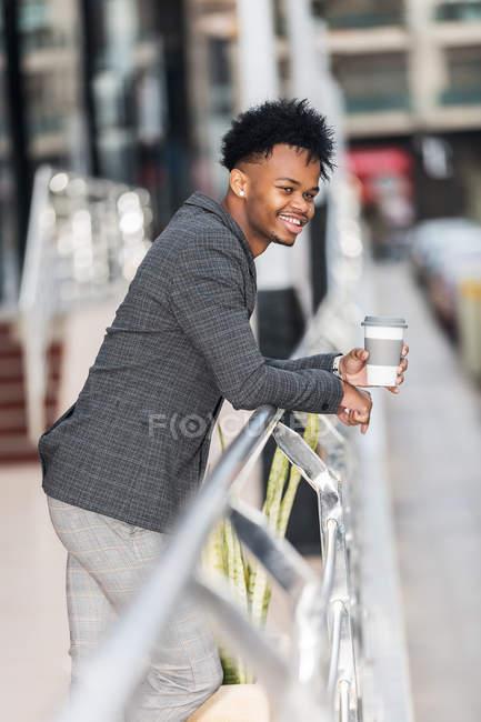 Вид сбоку на черного мужчину в модном костюме, улыбающегося и держащего чашку свежего горячего напитка, опирающегося на перила на размытом фоне городской улицы — стоковое фото