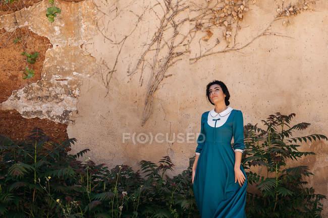 Mulher árabe atraente em vestido entre plantas perto da parede — Fotografia de Stock