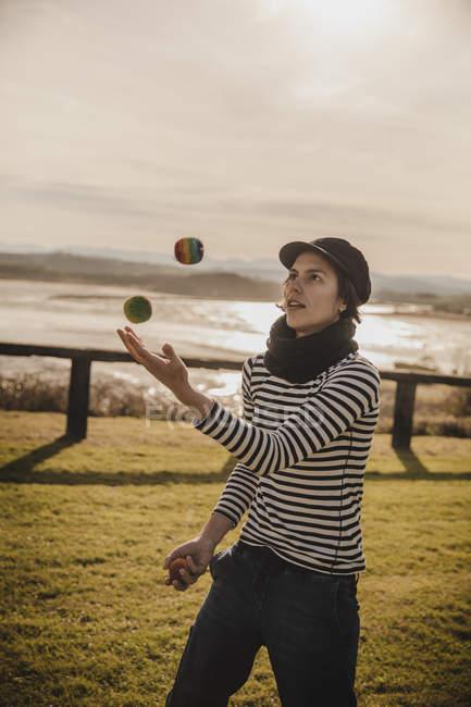 Elegante donna in berretto giocoleria palle su erba vicino alla costa del mare e del cielo con il sole — Foto stock