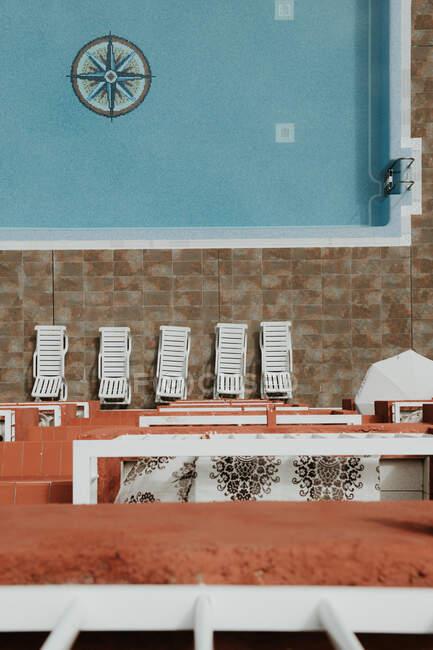 Dall'alto balcone vista delle sedie a sdraio poste a bordo piscina dell'hotel — Foto stock